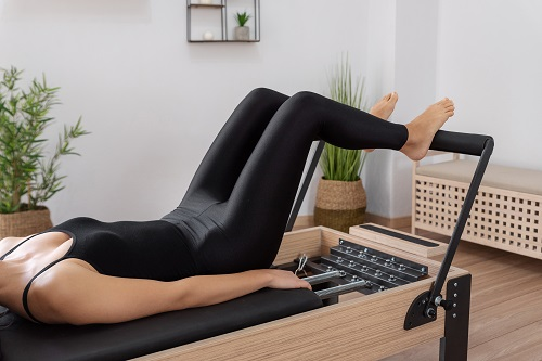 Long Stretchexercising on pilates reformer bed